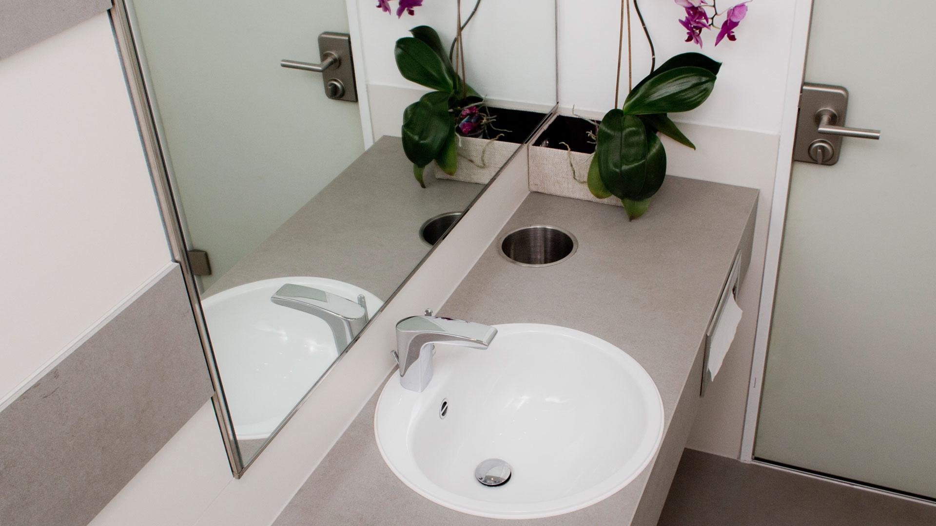 Maßangefertigter Waschtisch aus VidroStone mit Edelstahlöffnung für Papierkorb