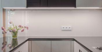 C-förmige Küche mit Spiegeleffekten dank Naturstein (Silestone Doradus poliert) und Hochglanzoptik der Küchenober- und Unterschränke