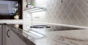 Diagonal verlegte Wandfliesen spiegeln sich in der Küchenarbeitsplatte aus Naturstein (ausgesucht im Böhm Steinwerk)