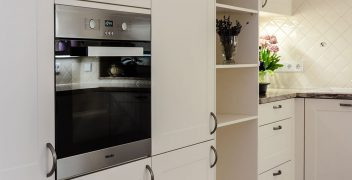 Raumhohe Schränke, ausgestattet mit ergonomisch angeordneten Einbauelementen wie Backofen Miele H2261-1BED und verstecktem Kühlschrank
