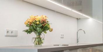 Brilliantweiße Küchenzeile mit designstarken Griffleisten aus Aluminium