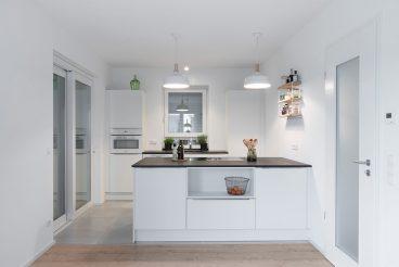 Schlichtes und stilvolles Küchendesign mit Hochschränken und Kochinsel mit weißen Fronten