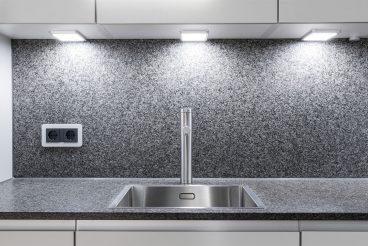 Minimalistisch designte Spüle von Caressi integriert in Küchenarbeitsplatte aus Naturstein