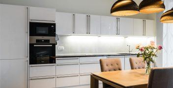 Polarweiße Küchenfront mit edelstahlfarbenen Stangengriffen