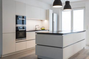 Edle Glasfronten in mattem Weiß verleihen der Küche Leichtigkeit und Eleganz