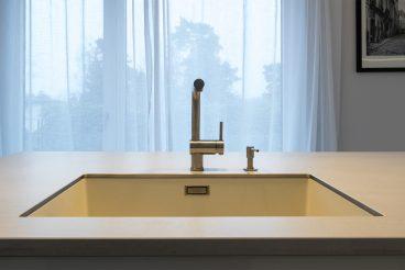 In Keramikarbeitsplatte eingelassenes Waschbecken von Blanco, dazu passende Armatur und Seifenspender von Grohe