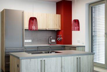 Ausgewählte Farbakzente verwandeln das schlichte Küchenmobiliar mit Oberflächen in dezentem grau und eiche sand in einen Ort voller Lebendigkeit und Vitatlität