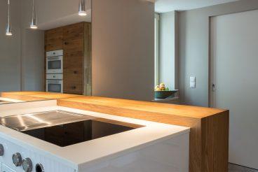 Stilvoller Übergang zwischen Kochinsel mit Keramikoberfläche und Kochfeld BORA Professional 2.0 und Bartresen aus Holz