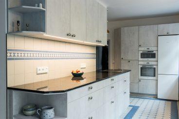 Klassische, nordisch angehauchte Fliesen an Wand und Boden treffen auf modernes Mobiliar mit Fronten in Betonoptik (LEICHT Küchen Ikono Keraton)