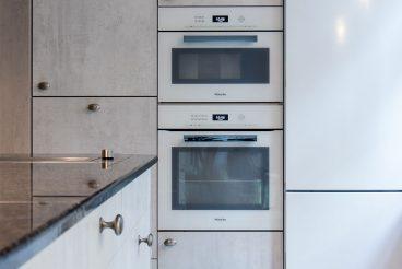 Hochschränke mit Fronten in Betonoptik fassen den kundeneigenen Kühlschrank ein
