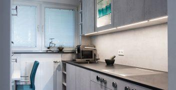Küchenunterschränke von LEICHT Küchen mit Fronten in Betonoptik und eine Küchenarbeitsplatte aus VidroStone Hightechkeramik über die gesamte Raumlänge nutzen jeden Zentimeter aus