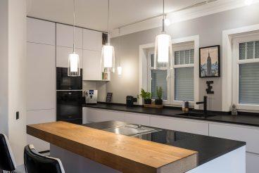 Grau in grau: Einladende Küche aus LEICHT Küchen Bondi-C, TEAM7-Bartheke und Natursteinarbeitsplatte in Nero assoluto