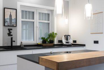 Zentral positionierter Küchenblock mit Natursteinarbeitsplatte und 8cm-starker Theke aus Eiche von TEAM7