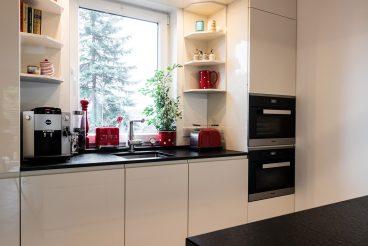 Optimal ausgenutzte Wand für Stauraum dank Hoch- und Oberschränken sowie Regalen (LEICHT Küchen Sirius – Magnolie)