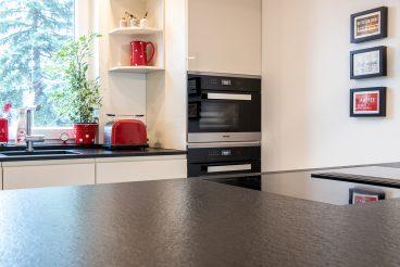 Exakt in Küchenarbeitsplatte aus Naturstein eingearbeitetes Miele TwoInOne-Kochfeld-Abzugssystem
