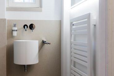 Trick zur optischen Vergrößerung des kleinen Raumes:  maßgeschneiderter LED-Spiegel, der über dem edlen Heizkörper Ganto von Nordholm positioniert wurde