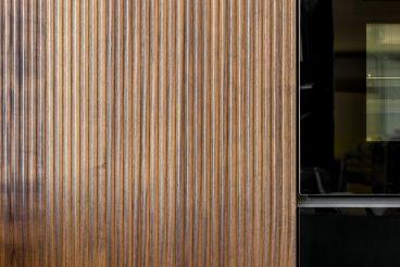 LEICHT Küchen BOSSA Concrete: Vertikale Stäbchen der Echtholzfront BOSSA in Walnuss sorgen für eine edle Haptik und Optik