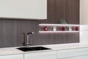 Perfekte Beleuchtung durch integrierte LEDs in Oberschrank und Wandbord bei unserer Musterküche LEICHT Fenix Evo