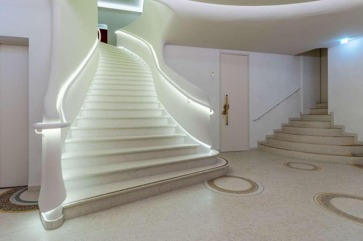 Design: Bennett + Böhme Vision, Foto: Alexander Kroeker – Mit Mosaik besetzte, einläufge, geschwungene helle Marmortreppe